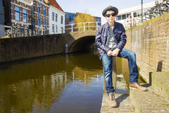 Cute teenage boy in hat  against canal bac. Cute teenage boy in hat (full-length portrait) against canal background Stock Photography
