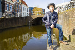 Cute teenage boy in hat (full-length portrait) on the dutch stre Royalty Free Stock Photos