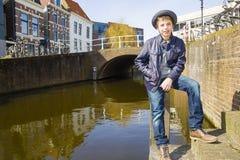Cute teenage boy in hat (full-length portrait) on the dutch stre. Et Royalty Free Stock Photos