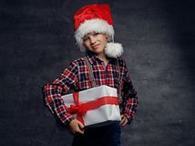 Teenage boy in Santa`s hat holds gift box. Cute teenage boy in Santas` hat dressed in a plaid shirt holds big present gift box Stock Images