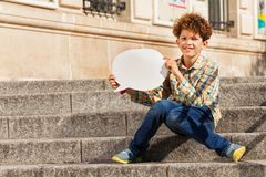 Cute teenage boy with blanked speech bubble. Cute teenage boy sitting on the stairs outdoors, holding blanked speech bubble Stock Images