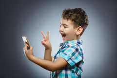 Cute teenage boy taking selfie on grey background.  Stock Photos