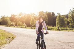 Cute teenage boy wearing shirt carrying backpack riding his bicycle having rest during his ride in suburb of city. Young schoolboy Royalty Free Stock Images