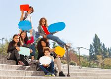 Cute teenage boys and girls holding speech bubbles. Group of teenage boys and girls sitting on the stairs outdoors, holding blanked speech bubbles Stock Images