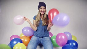 Cute teenage girl with balloons in bright studio. Happy beautiful girl with balloons looking at camera