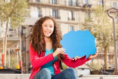 Cute teenage girl with blanked speech cloud. Cute teenage girl sitting on the stairs outdoors, holding blanked speech cloud Stock Photo