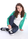 Cute teenage girl with blue eyes sits on floor stock images