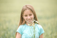 Cute teenage girl with charming smile picking daisies Stock Photography
