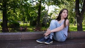 Cute teenage girl checking phone and waiting phone call sitting in park. Video footage HD shooting static camera. Cute teenage girl checking cellphone and stock video