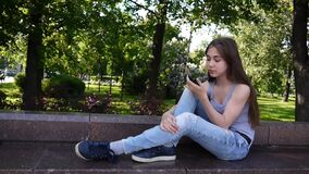Cute teenage girl checking phone and waiting phone call sitting in park. Video footage HD shooting static camera. Cute teenage girl checking cellphone and stock video footage