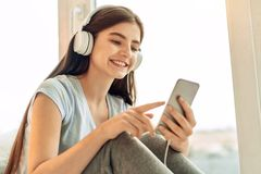 Cute teenage girl choosing music to play. Best music. Beautiful teenage girl scrolling her playlist and choosing the songs to play while listening to the music Stock Photo