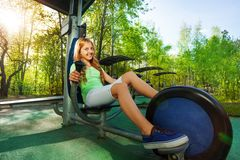 Cute teenage girl cycling on exercise equipment Stock Image