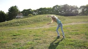 Cute teenage girl doing cartwheel at green meadow stock video footage