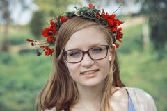 Cute teenage girl with glasses and a wreath of spring flowers Royalty Free Stock Photos