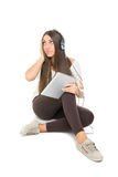 Cute teenage girl with headphones listening music on tablet Stock Photography