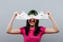 A cute teenage girl in her skirt holding up her shoes with a confused expression on her face. stock photography
