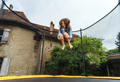Cute teenage girl jumping on trampoline Royalty Free Stock Photography