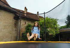 Cute teenage girl jumping on trampoline Stock Image