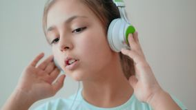 Cute teenage girl listening to music through headphones stock video footage