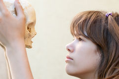 Cute teenage girl looking at human skull Stock Image