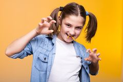 Cute teenage girl making fangs from food. In studio photo on yellow background Royalty Free Stock Images