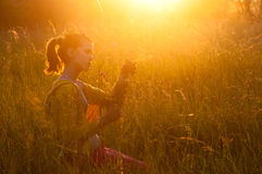 Cute teenage girl picking flowers on the meadow. On sunny spring day Royalty Free Stock Images