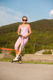 Cute teenage girl in pink dress on scooter Stock Photo