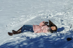 Cute teenage girl playing in white snow Stock Image