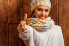 Cute teenage girl. Portrait of a cute teenage girl in a scarf and a cap showing a handgun, looking in camera and smiling, standing on a wooden background Royalty Free Stock Images