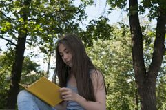 Cute teenage girl reading book sitting on the bench in park, studying outdoor. Stock Photos