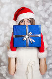 Cute teenage girl with Santa hat holding blue gift box against snow background Stock Photo