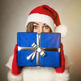 Cute teenage girl with Santa hat holding blue gift box Royalty Free Stock Photo