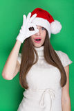 Cute teenage girl with Santa hat looking on one eye Stock Photos