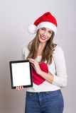 Cute teenage girl with Santa hat showing tablet computer Stock Image