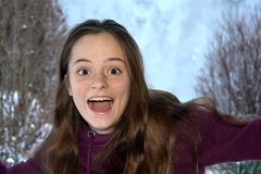 Cute teenage girl screams with joy. Surprised teenage girl , she screams loudly for joy with her eyes and mouth wide open royalty free stock photo