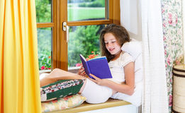 Cute teenage girl siiting on window siil Stock Image