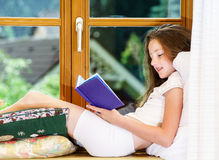 Cute teenage girl siiting on window siil Stock Photography