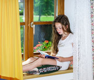 Cute teenage girl siiting on window siil Royalty Free Stock Photos