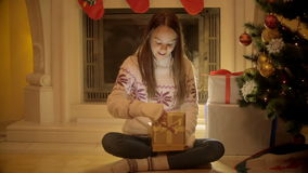 Cute teenage girl sitting at fireplace and opening Christmas gift box stock video footage