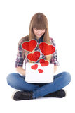 Cute teenage girl sitting and sending love messages with laptop Stock Images
