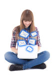 Cute teenage girl sitting and sending messages with laptop isola Royalty Free Stock Photos