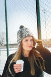 Cute teenage girl speaking on the phone. Cute happy blonde Caucasian teenage girl speaking on the phone outdoors. Woman holding coffee cup wearing knitted beanie Stock Image
