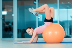 Cute teenage girl at sports club. Happy to be fit. Portrait of attractive teenage girl lying on fitness ball and smiling at camera while training in sports club stock photography