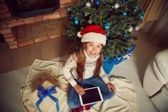 Cute teenage girl near Christmas tree Royalty Free Stock Photos