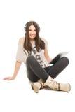 Cute teenage girl with tablet listening music on headphones Stock Photo