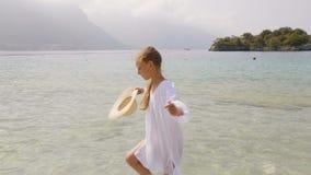 Cute teenage girl in wicker hat walking at seashore stock video