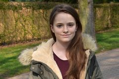 Cute teenage girl with winter jacket. Portrait of a pretty teenage girl with freckles, wearing a modern winter parka stock photo