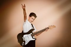 Young guitar player with hand up showing sign of horns. Cute teenage guitar player with hand up showing sign of horns on the stage royalty free stock photography