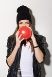 Cute teenage hipster girl with a red balloon. Cute attractive Caucasian teenage hipster girl blowing a red balloon wearing leather jacket and beanie hat stock photography