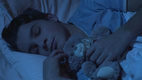 Cute teenage male sleeping in bed with teddy-bear toy, childhood, sweet dreams stock video footage